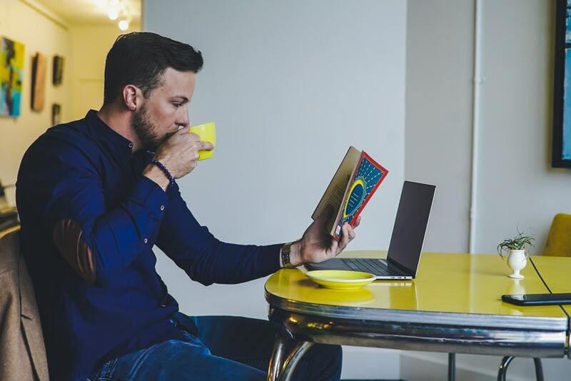 コーヒー飲ながら本を読むおじさん